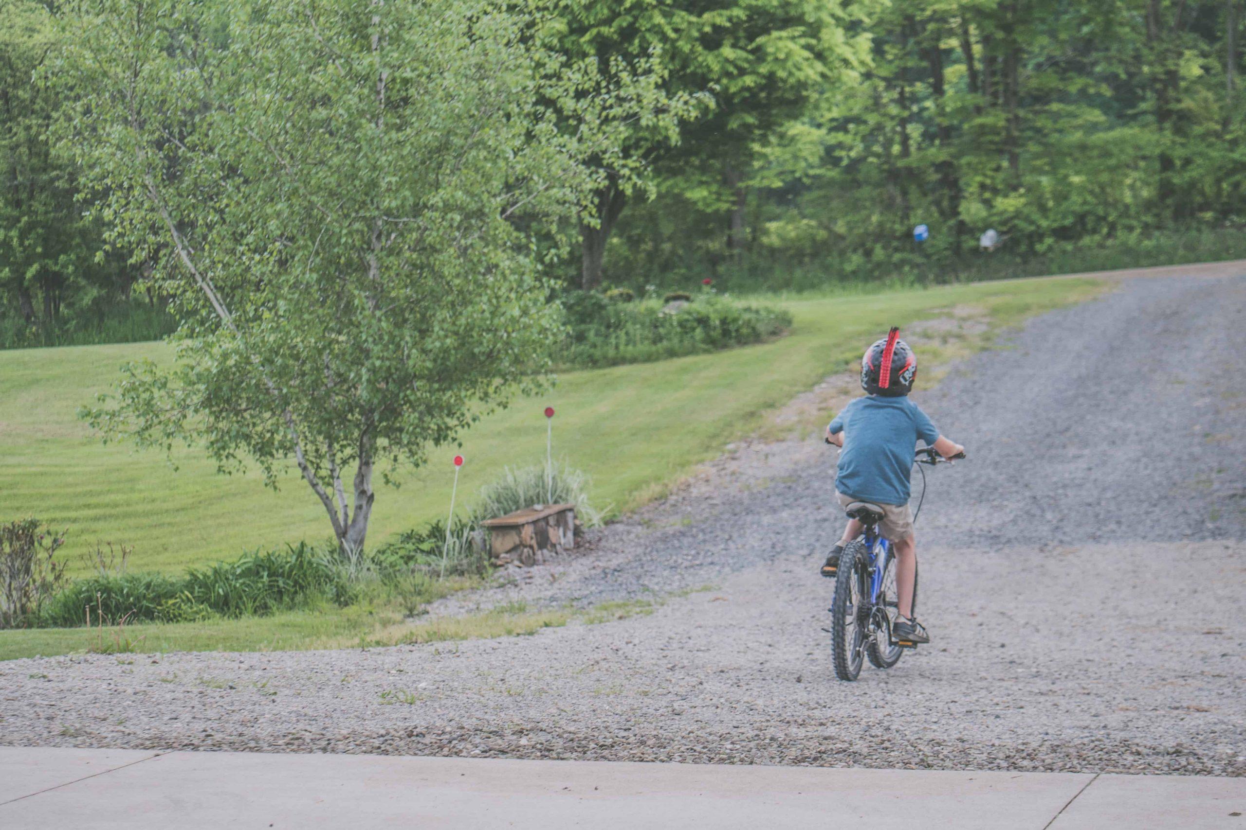 A imagem mostra as costas de menino de capacete pedalando numa estrada de cascalho. Ao fundo, uma cerca-viva.
