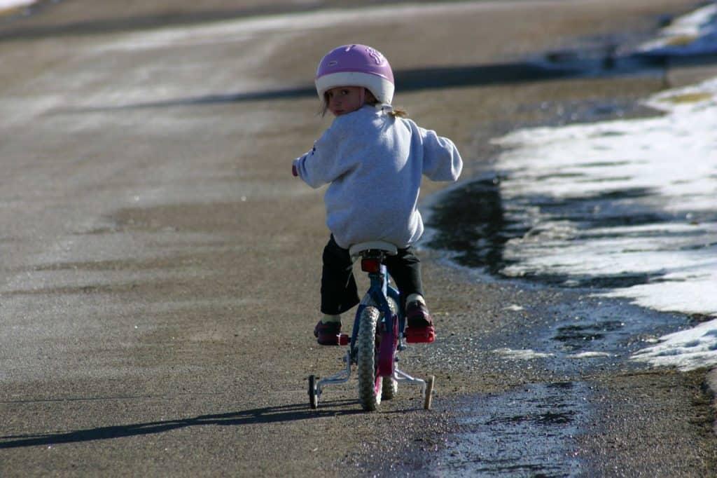Imagem de criança com capacete andando em bicicleta com rodinhas.