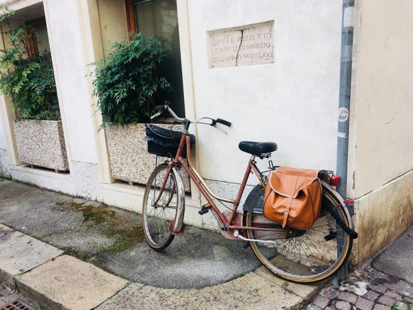 Bicicleta retrô com cesta e bolsa no bagageiro, estacionada na rua.