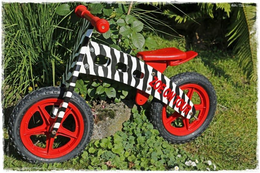 Imagem mostra uma bicicleta sem pedal de madeira com design e cores de zebra.