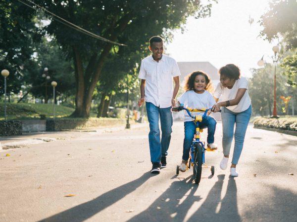 Imagem de uma menina em cima de uma bicicleta de rodinhas azul e amarela com dois adultos, um homem e uma mulher, a ajudando.