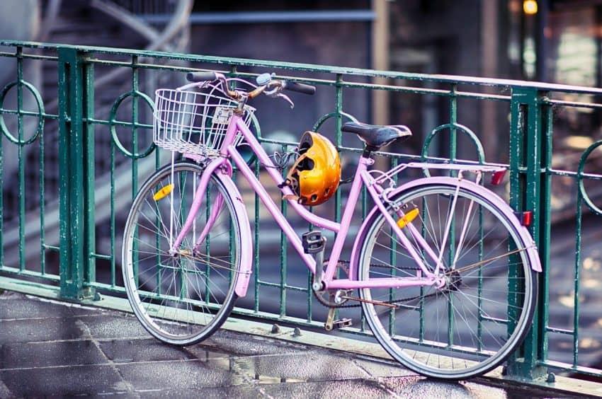 Bicicleta feminina rosa, com cestinha e capacete, presa na grade.