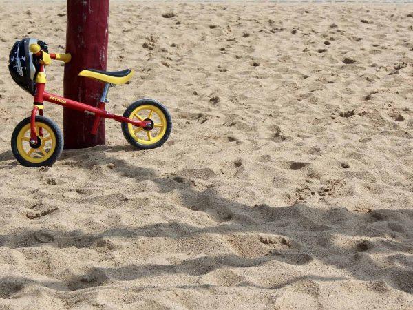 Imagem mostra uma bicicleta sem pedal encostada em um pilar de madeira na areia da praia.
