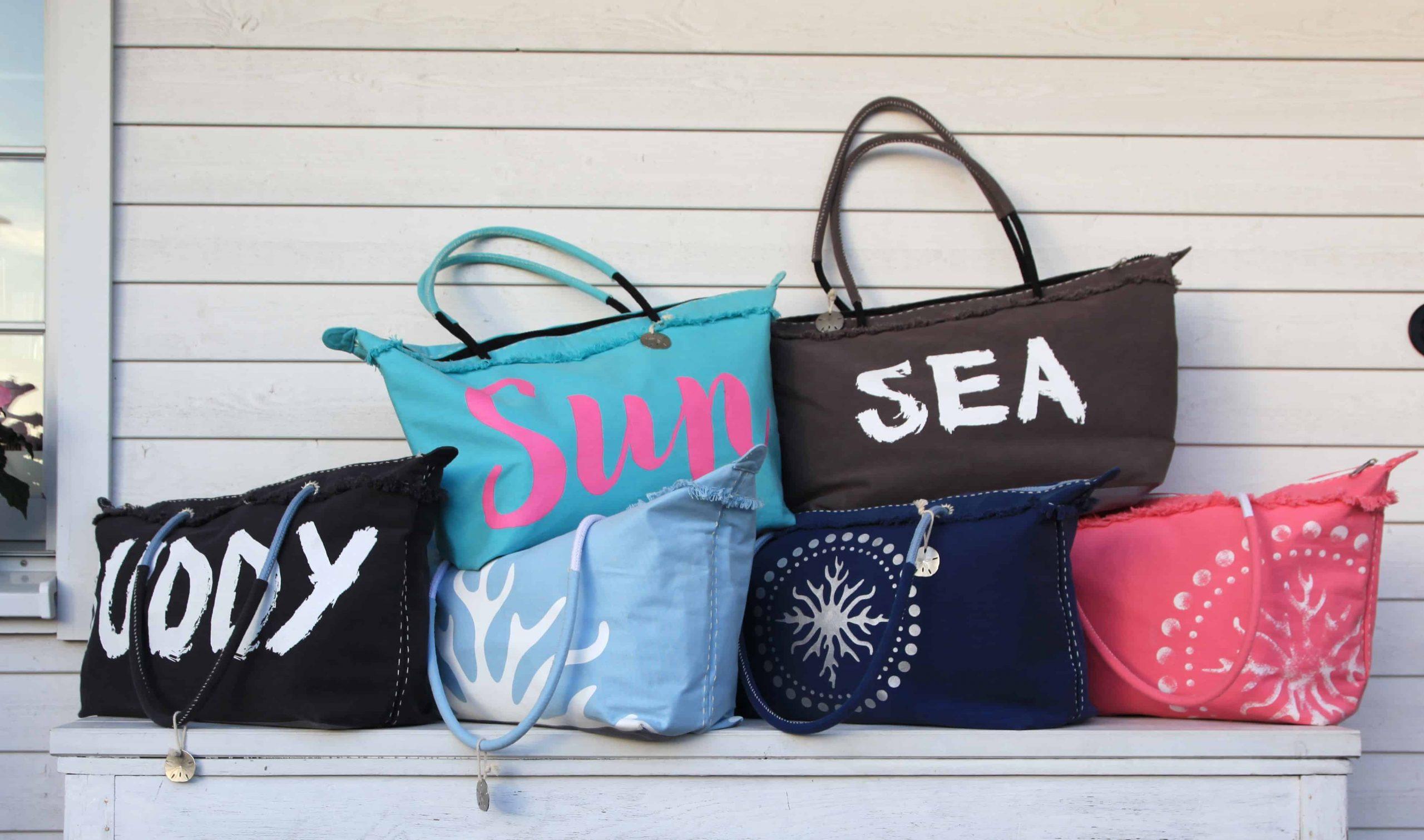 Foto de seis bolsas de praia grandes e amontoadas, com diferentes cores e estampas, encostadas em uma parede branca.