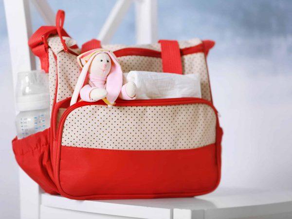 Bolsa maternidade vermelha e branca, com mamadeira e uso de pelúcia.