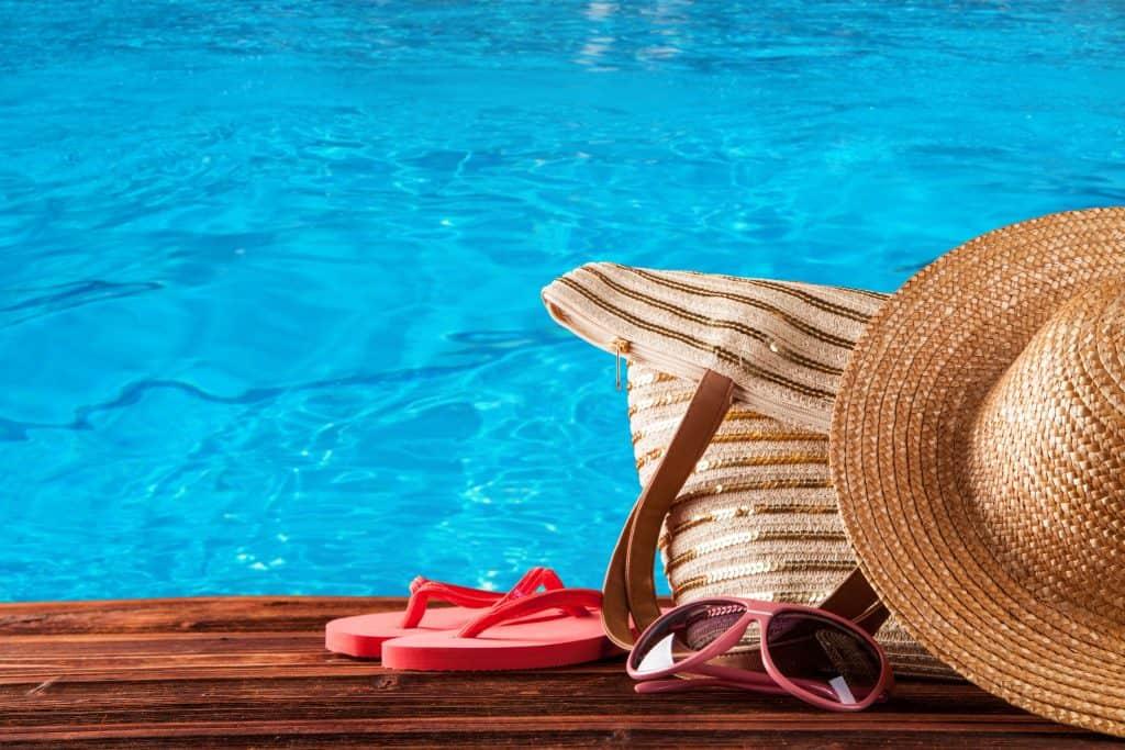 Foto de mostra bolsa de palha ao lado de óculos, chinelo e chapéu perto de piscina.