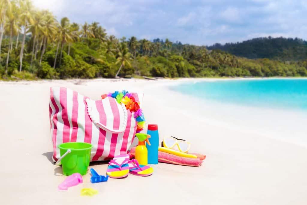 e60c10a90 Foto de uma bolsa de praia listrada na areia da praia com objetos ao redor.