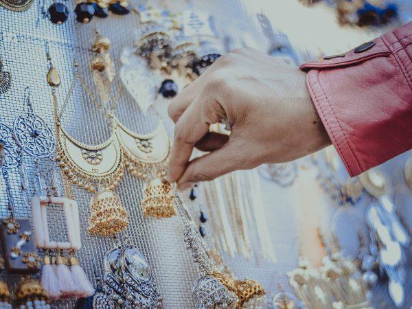 Imagem mostra diversos brincos expostos e uma mão encostando em um deles.