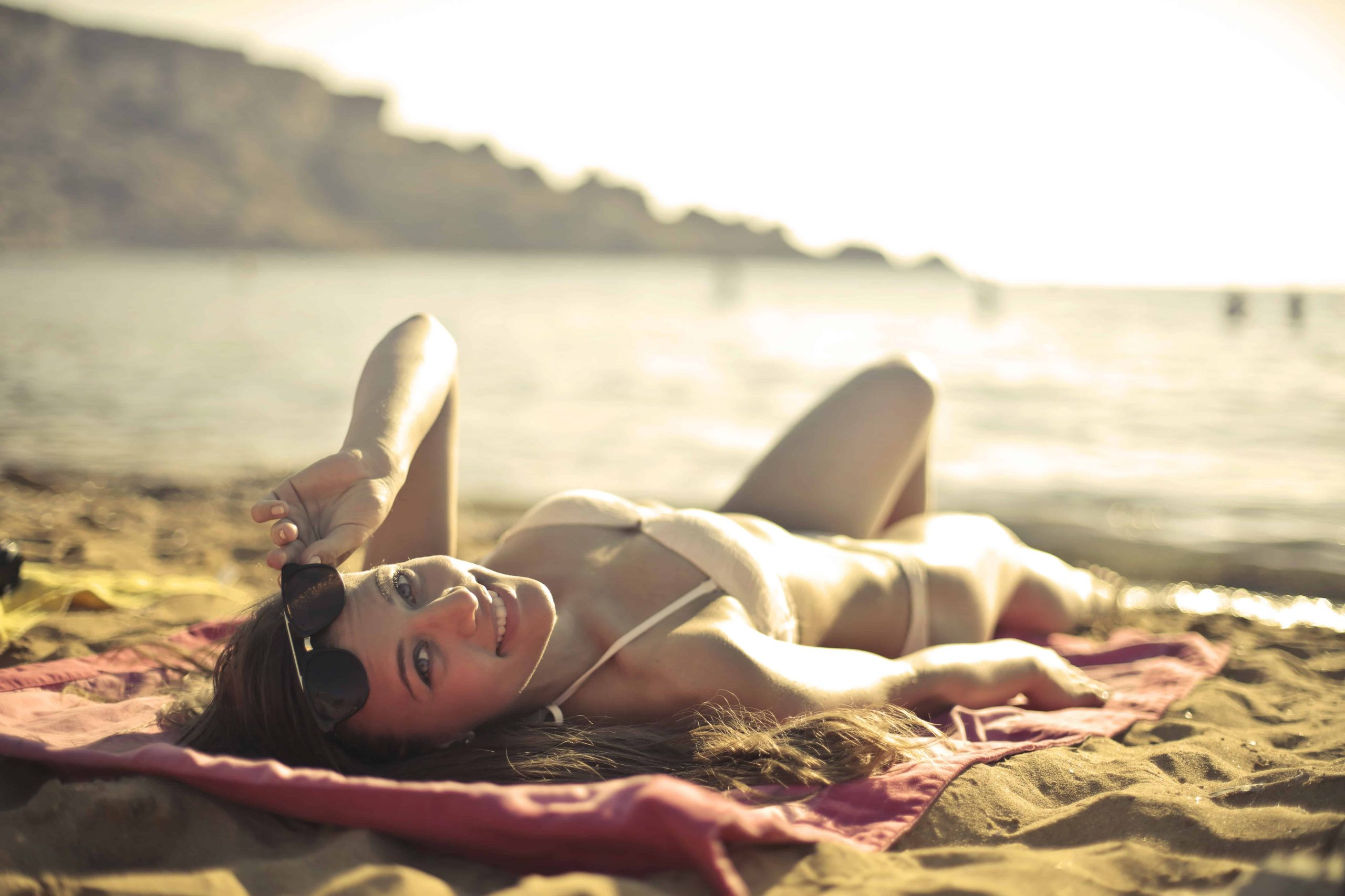 Foto de uma mulher de biquíni, deitada em uma toalha, na praia, se bronzeando. Ela segura o óculos de sol enquanto olha para a câmera.