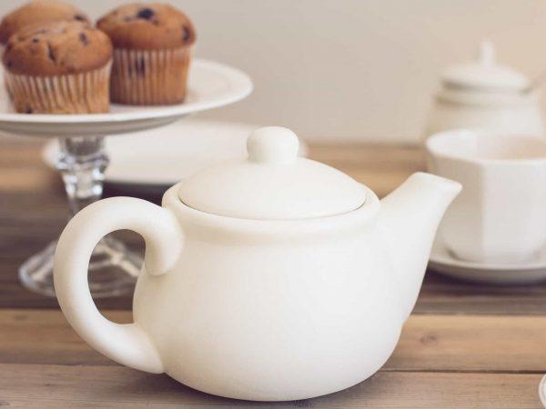 Imagem mostra uma mesa de chá da tarde, com bolinhos, xícaras e um bule branco retrô em destaque.