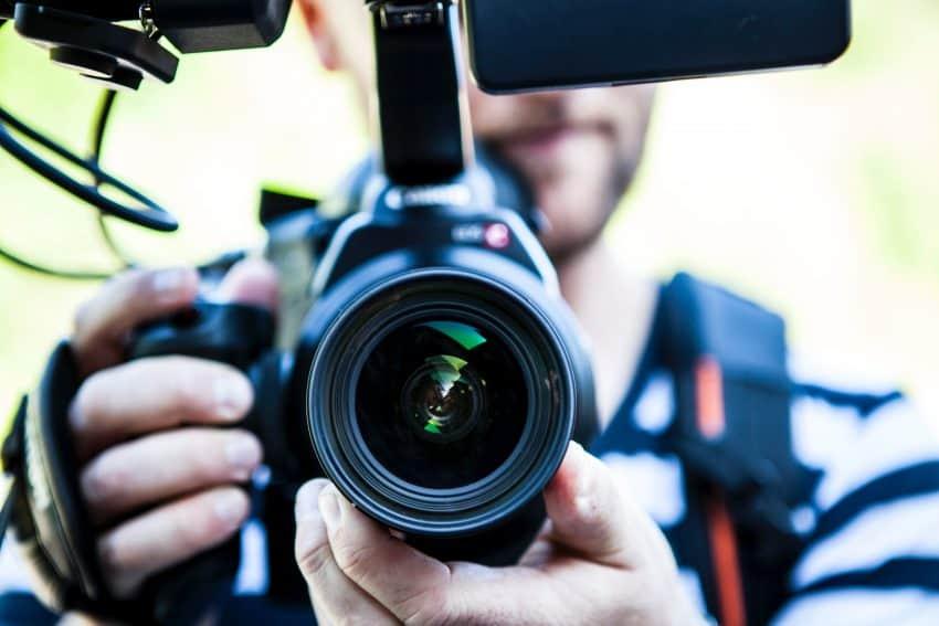 Na imagem é possível ver um close em uma pessoa com uma filmadora.