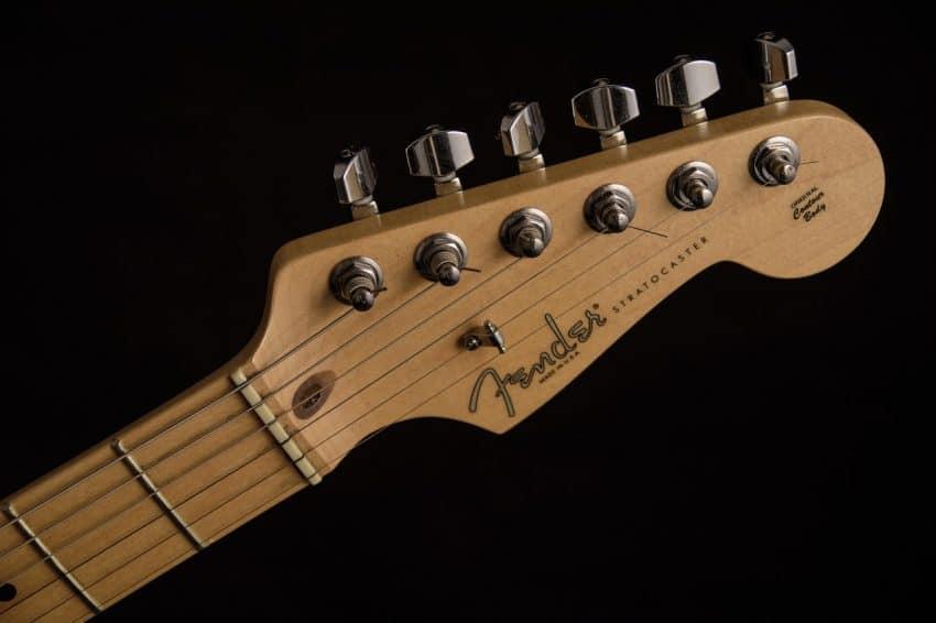 Imagem mostra cabeça de guitarra e cordas.
