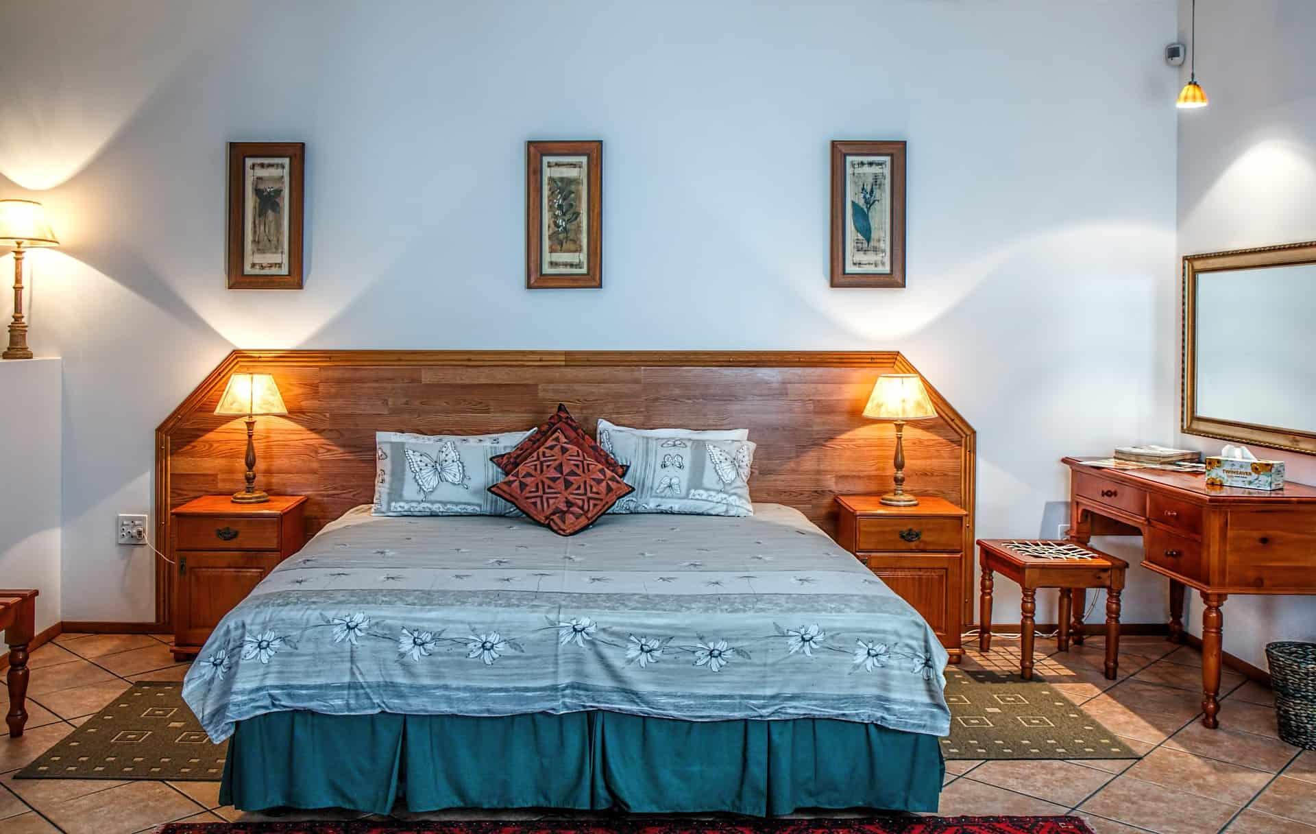 Imagem de cama com cabeceira com lençol azul e travesseiros com cabeceira de madeira iluminada por abajures.