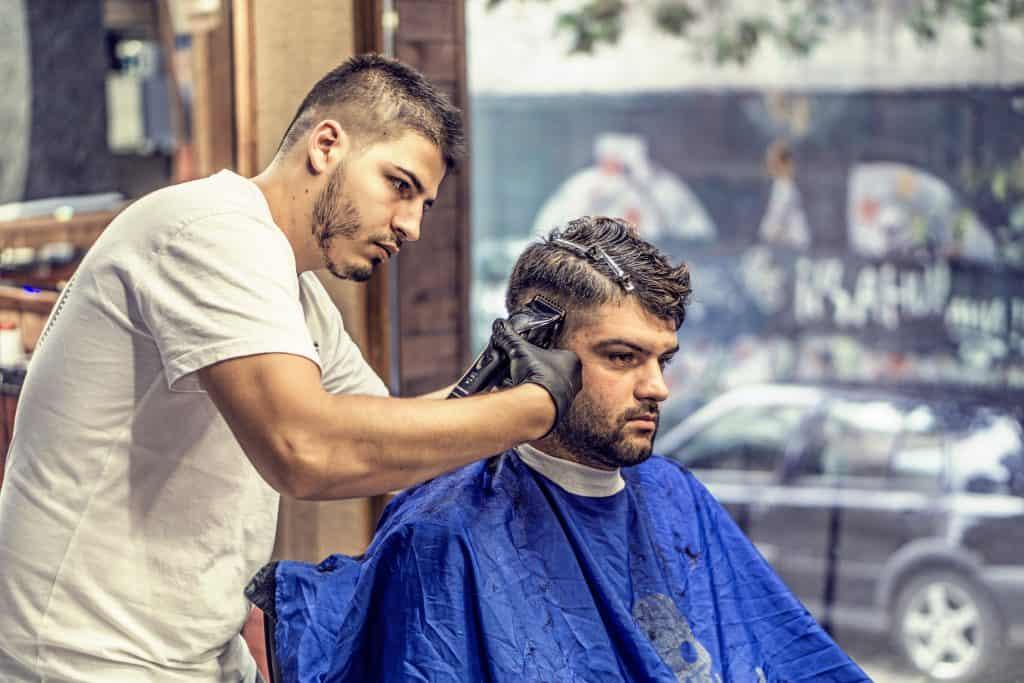 Imagem mostra um rapaz tendo os seus cabelos cortados por um barbeiro.