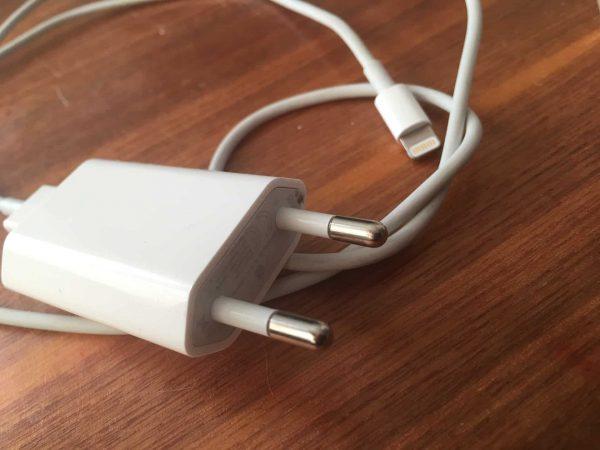 Imagem de um carregador e cabo de iPhone sobre uma mesa.