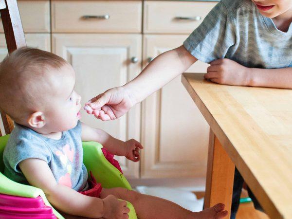 Imagem de bebê sendo alimentado, sentado em uma cadeira de alimentação.
