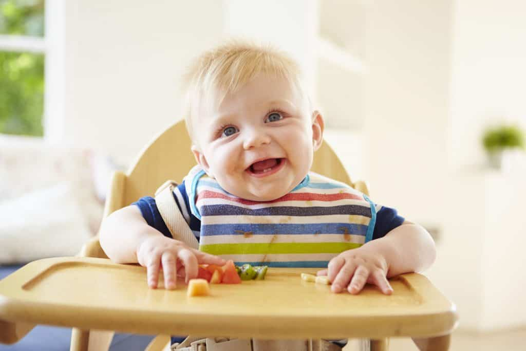 Smiling boy eating in wooden feeding chair.