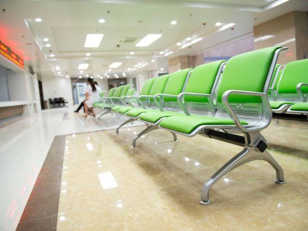 Cadeira longarina verde em uma sala de espera de hospital.