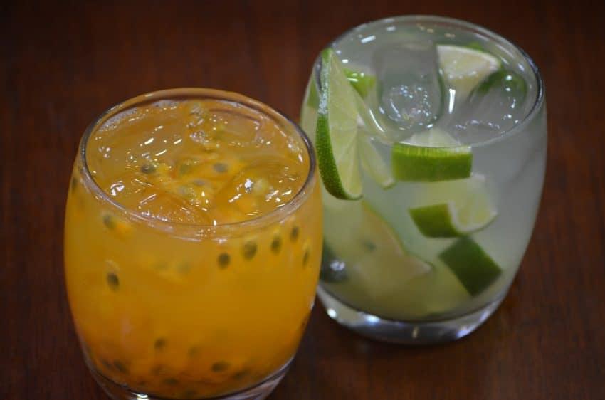 Foto de um drink de limão e hortelã, em um copo de vidro, com açúcar na beirada. Ao fundo, um limão cortado.