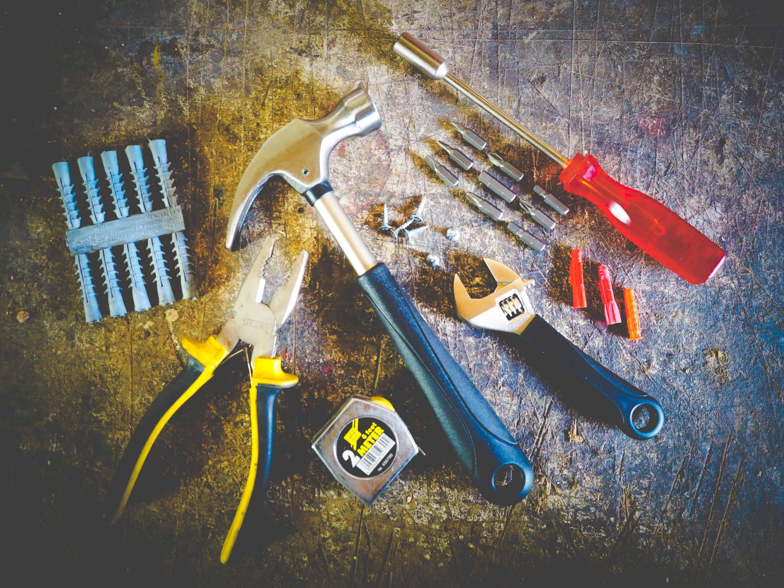 A imagem mostra ferramentas diversas dispostas sobre uma madeira gasta.