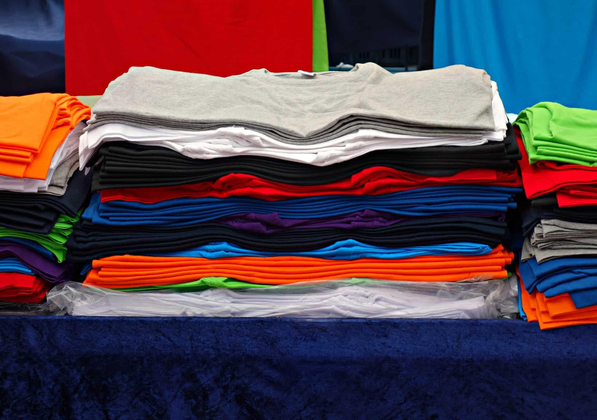 Diversas pilhas de camiseta UV com cores diferentes.