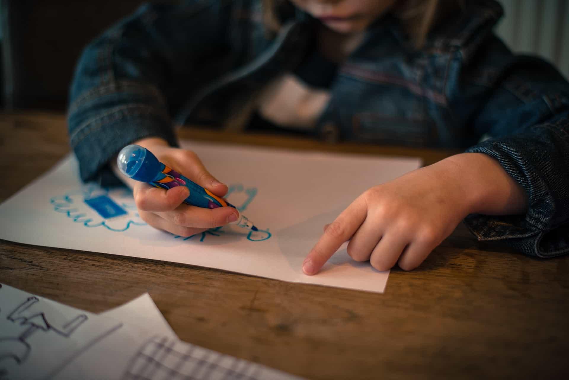 Imagem de criança desenhando em papel com uma caneta hidrográfica azul sobre mesa de madeira.