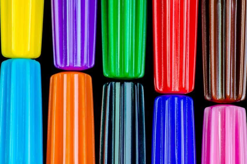 Imagem de tampas de canetas hidrográficas coloridas sobre mesa branca.