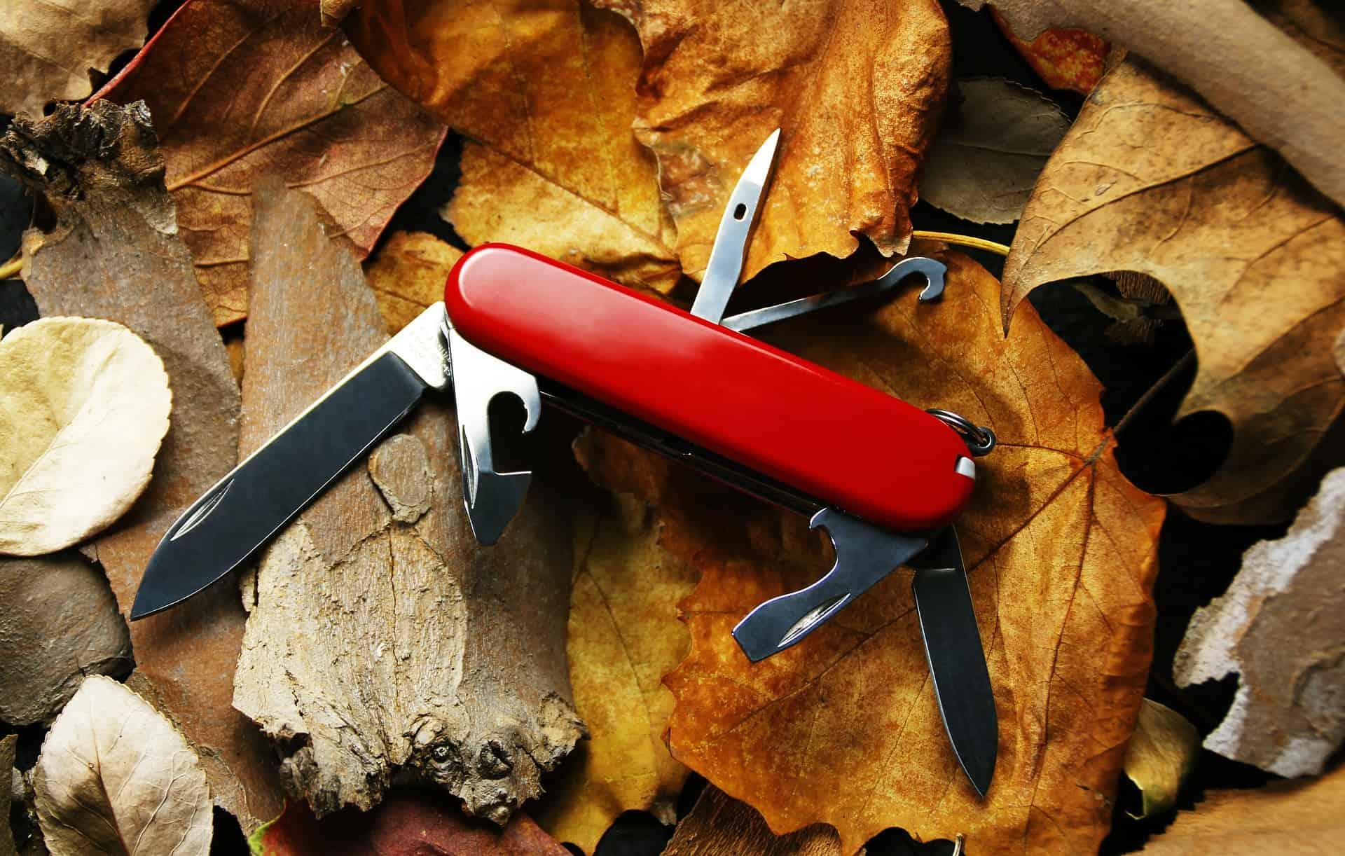 Canivete suíço, aberto e em cima de algumas folhas e pedaços de madeira.