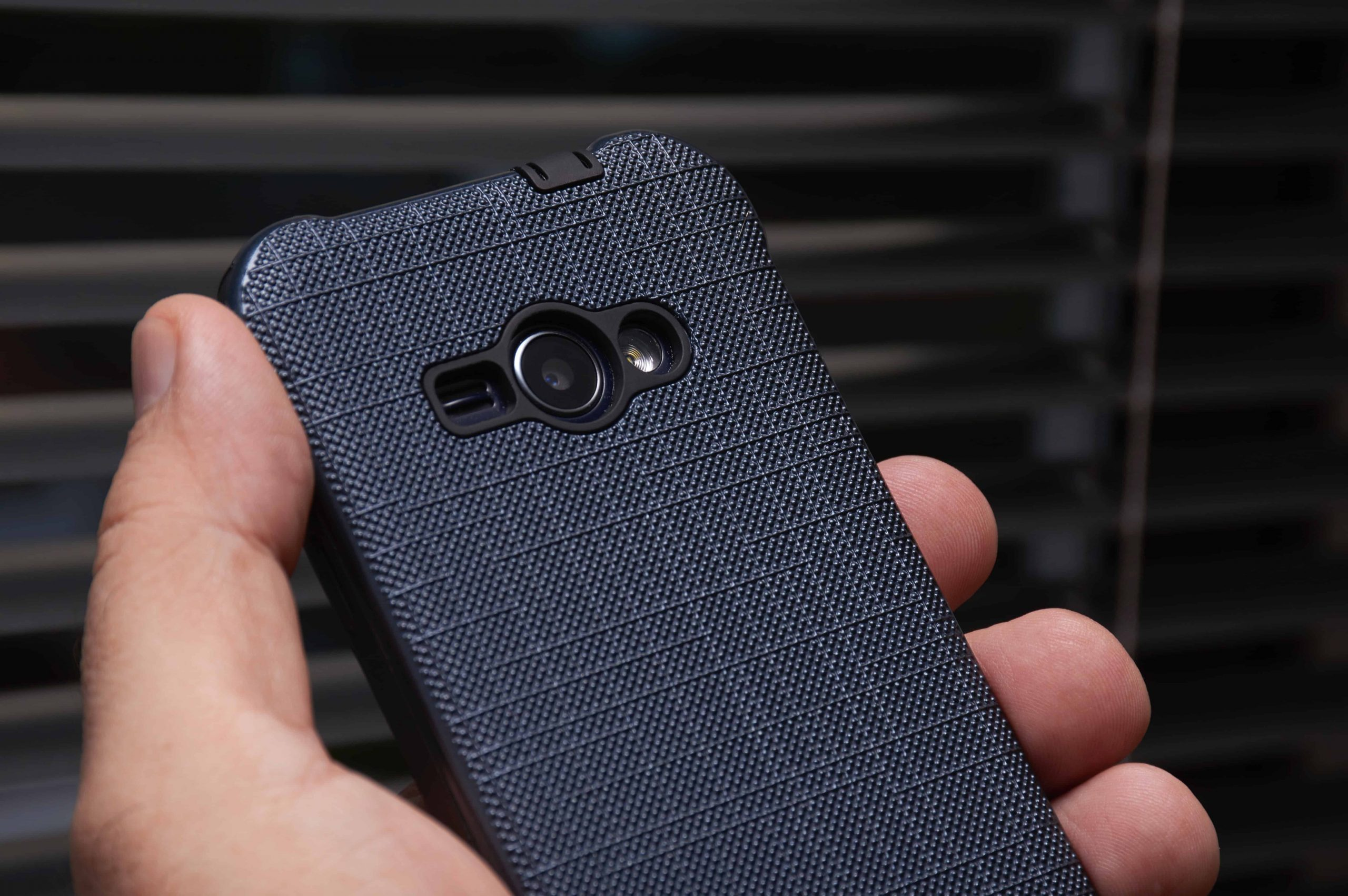 Foto de uma mão, aparentemente masculina, segurando um telefone celular com uma capinha azul escura e detalhes pretos.