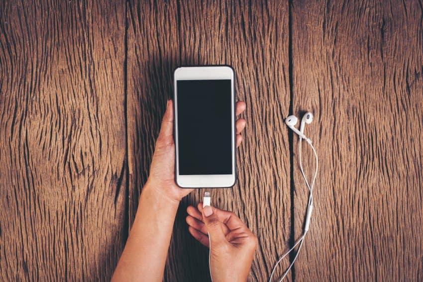Imagem de uma pessoa colocando seu iPhone para carregar.