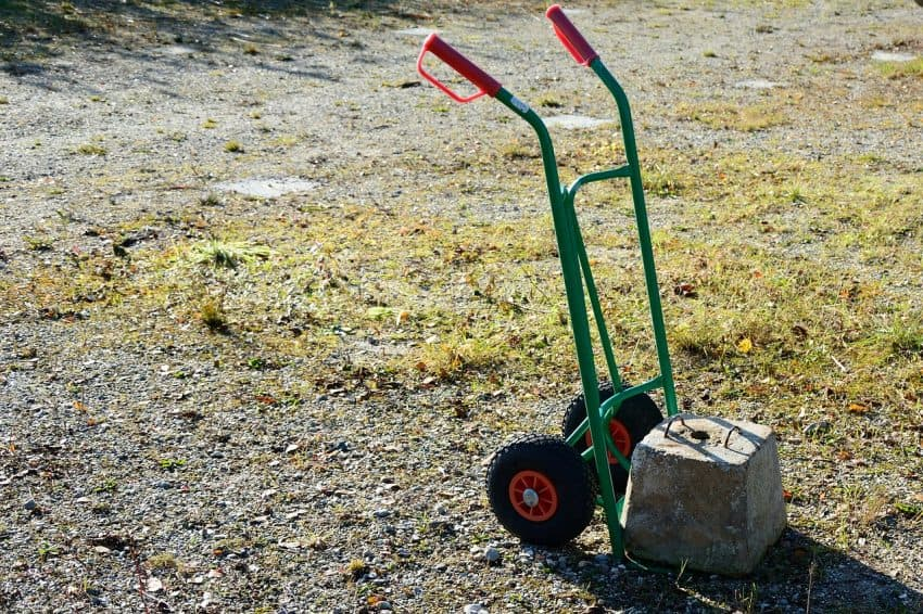 Um carrinho de mão para cargas em uma área abertas com pedras e grama carregado com um bloco de concreto.