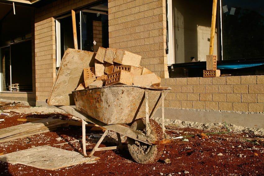 Imagem de um carrinho de mão velho carregado de tijolos.