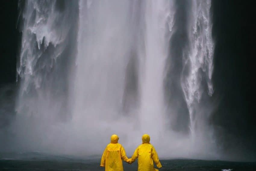 Imagem de duas pessoas de costas com capa de chuva amarela observando queda d`água.