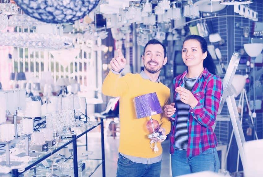 Casal em uma loja de iluminação escolhendo um lustre.