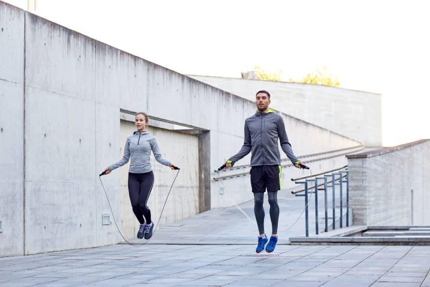 Duas pessoas se exercitando pulando corda ao ar livre.
