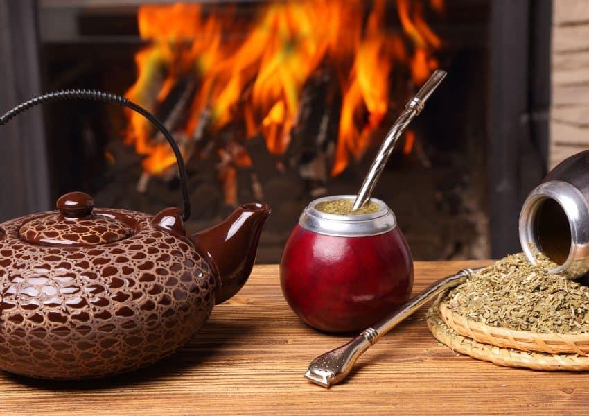 Imagem de uma cuia com chimarrão, chaleira com água e erva.