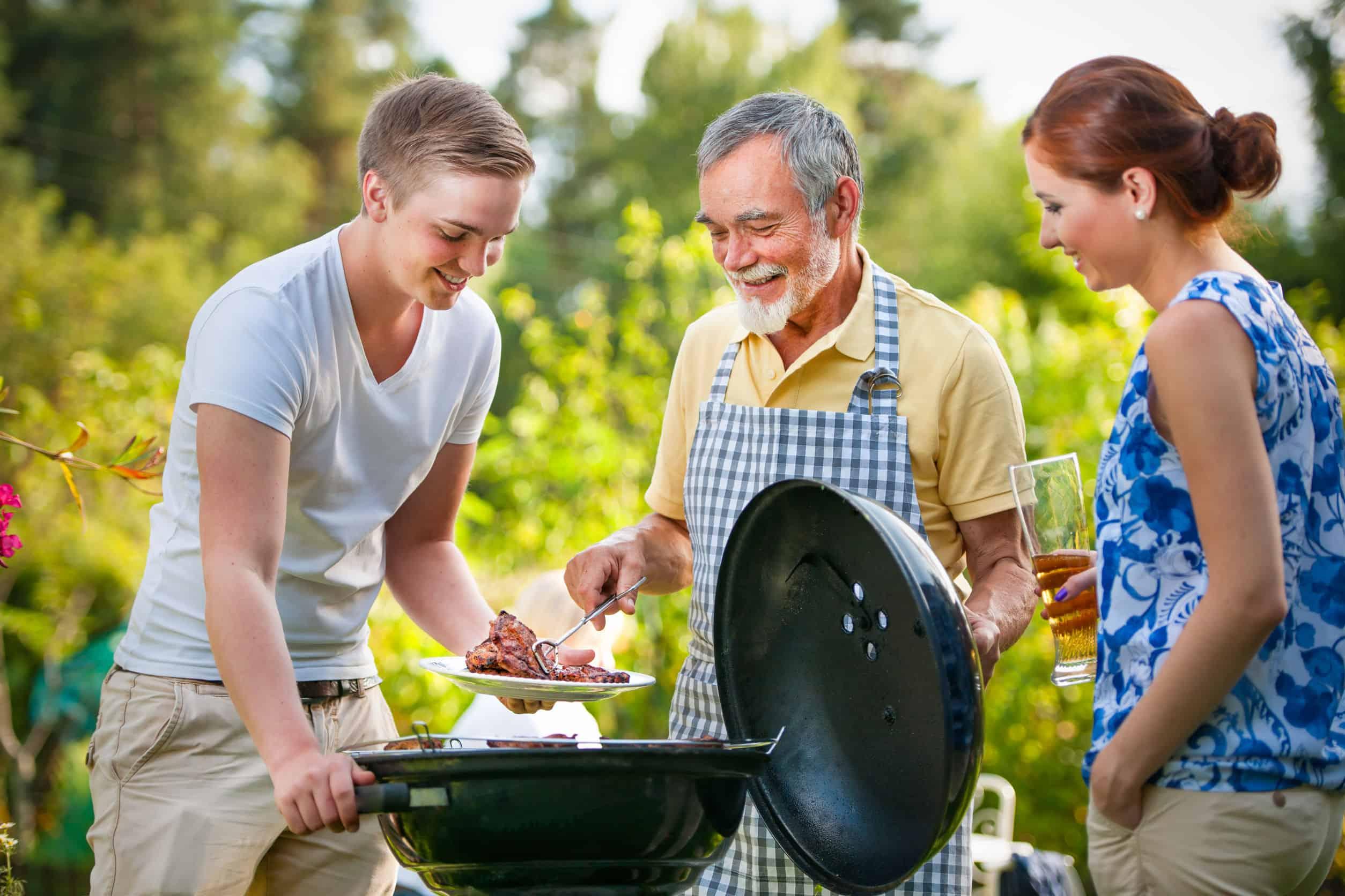 Imagem mostra três pessoas em volta de uma churrasqueira a bafo no jardim.