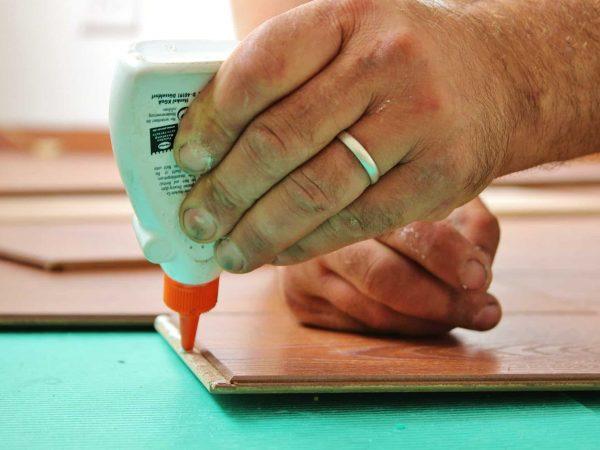 Imagem mostra uma mão humana aplicando cola em um pedaço de madeira.