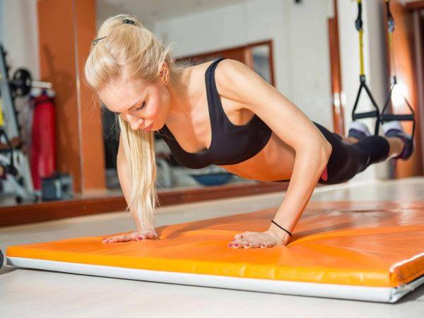 Mulher fazendo exercício de flexão sobre um colchonete laranja.