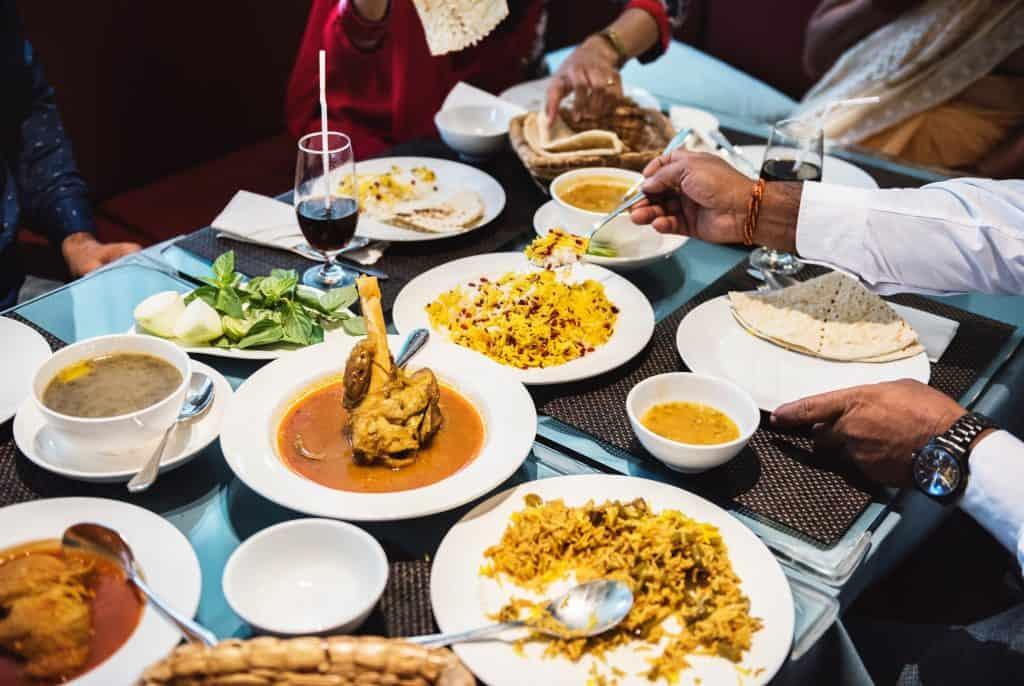 Imagem com diversos pratos de comidas chinesas e pessoas comendo.