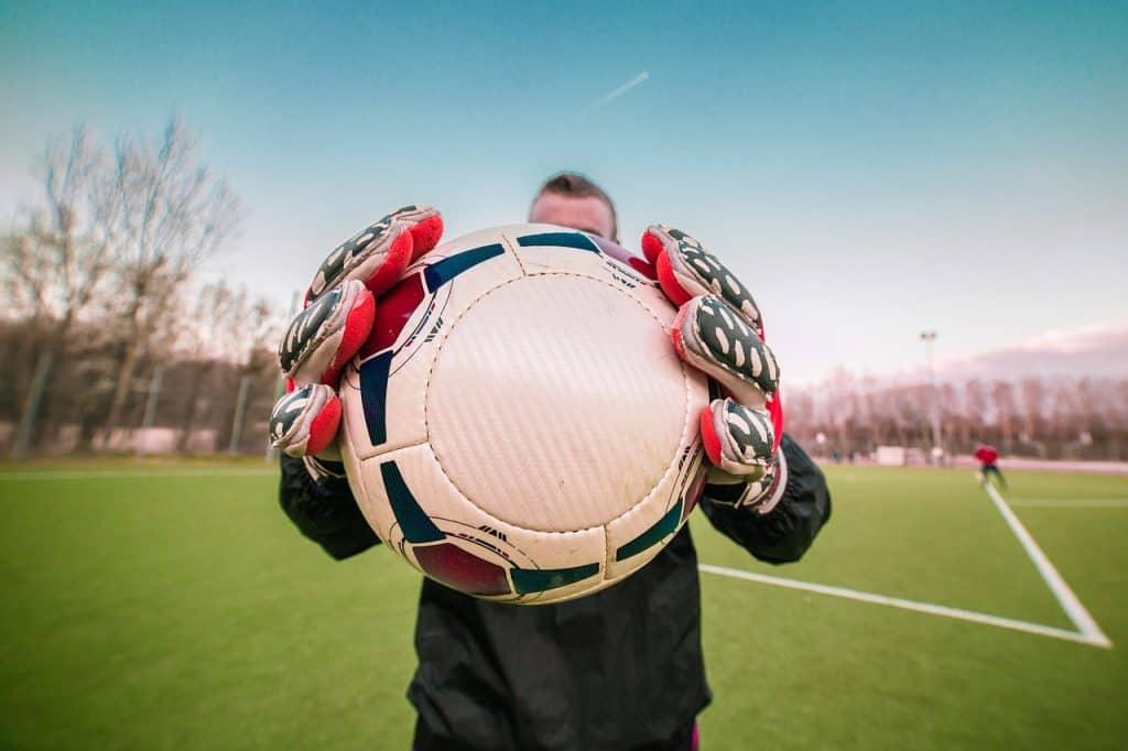 Imagem de goleiro com luvas de goleiro segurando bola de futebol