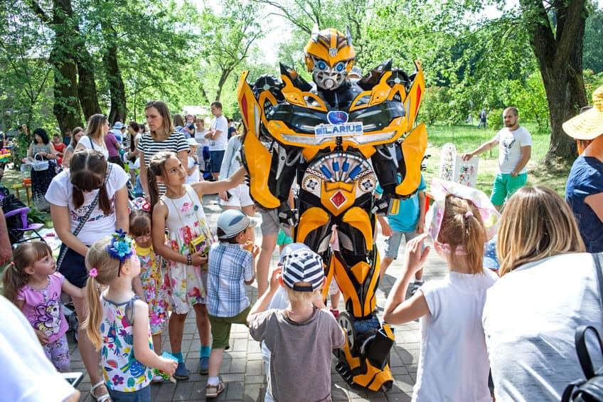 Imagem mostra um grupo de crianças junto com um ator fantasiado do personagem Bumblebee.