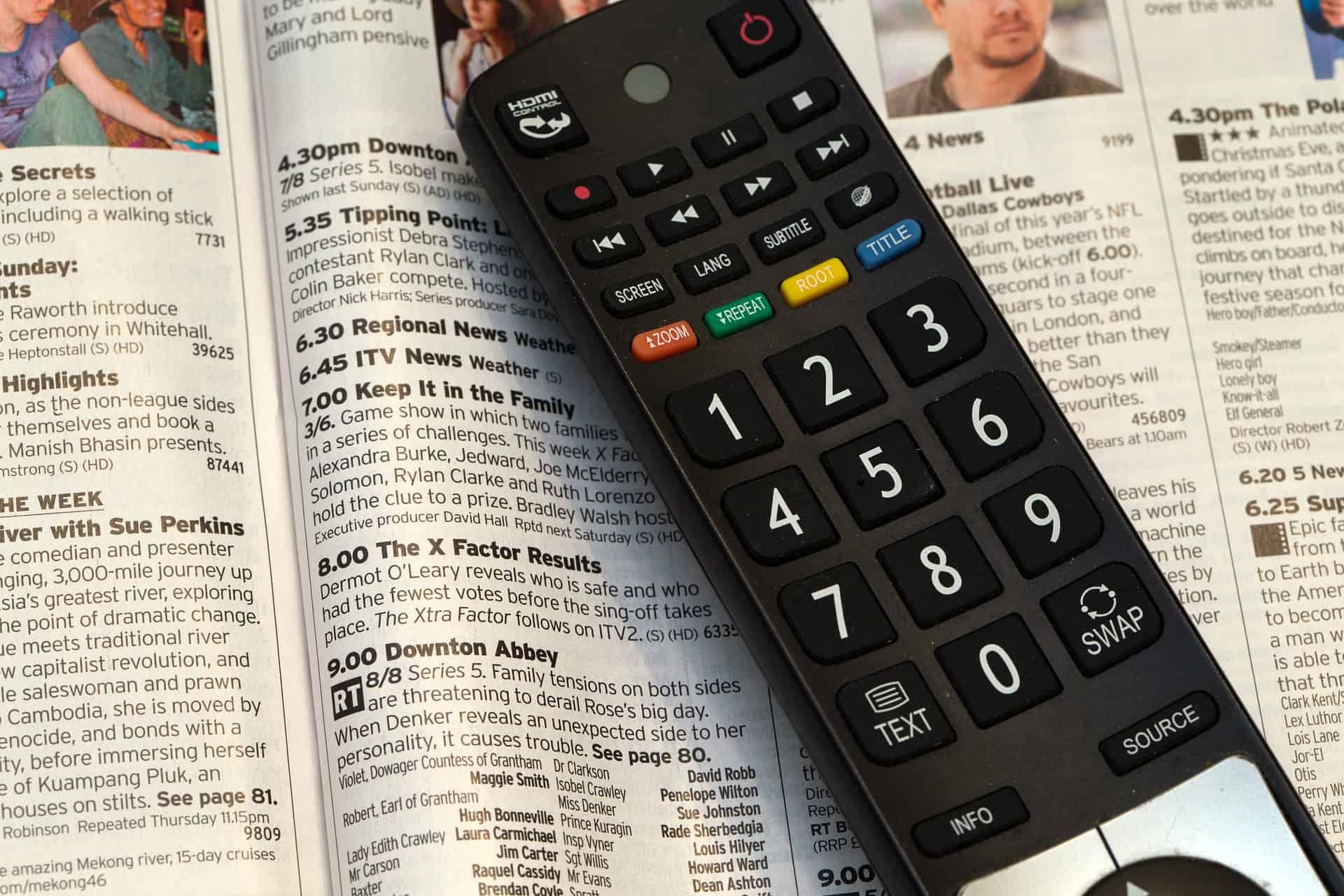 Um controle remoto em cima de uma revista aberta.