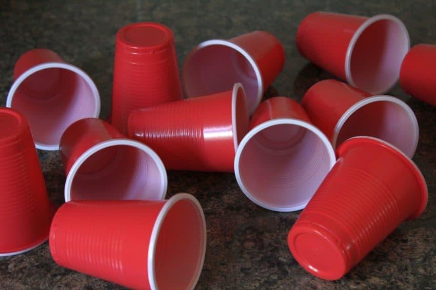 Copos descartáveis de plástico jogados no chão.