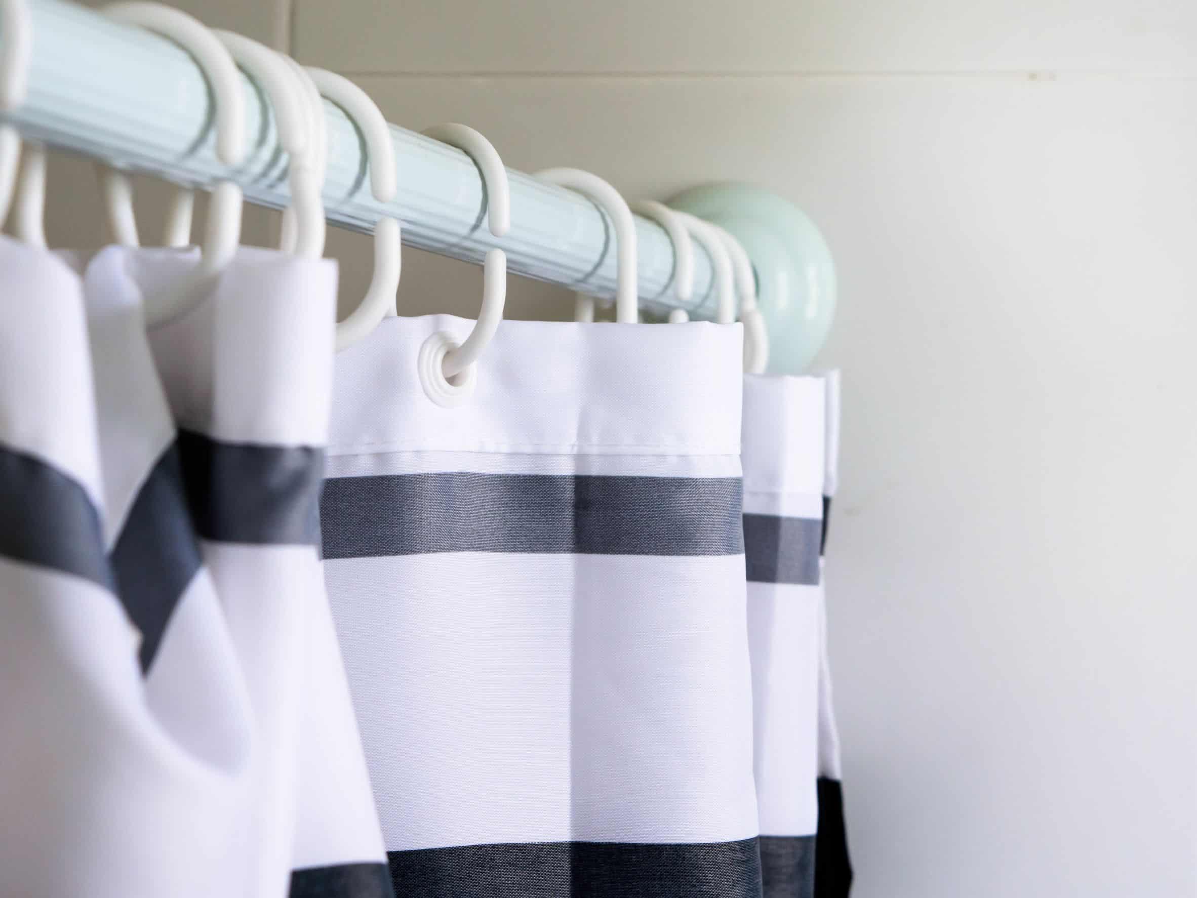 Foto de uma cortina branca, com listras pretas, presa no box de um banheiro.