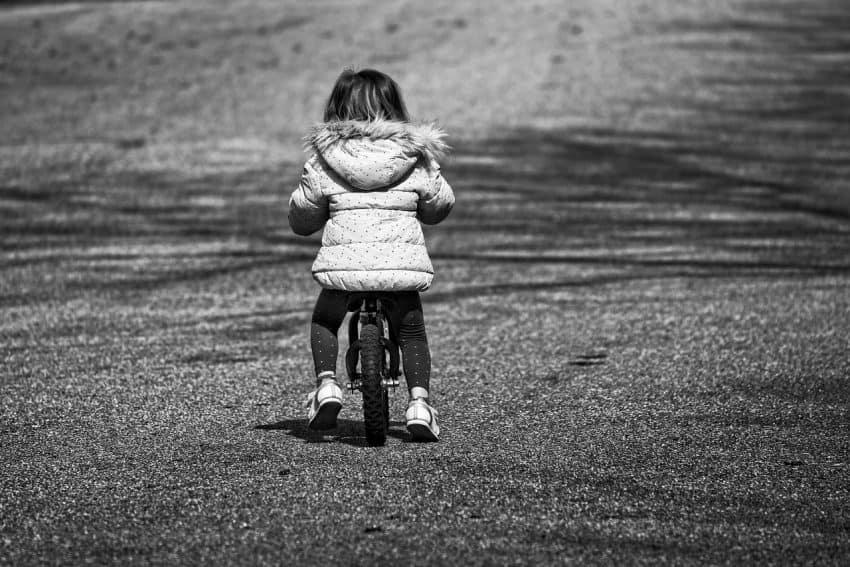 Imagem de uma criança de costas andando com uma bicicleta sem pedal.