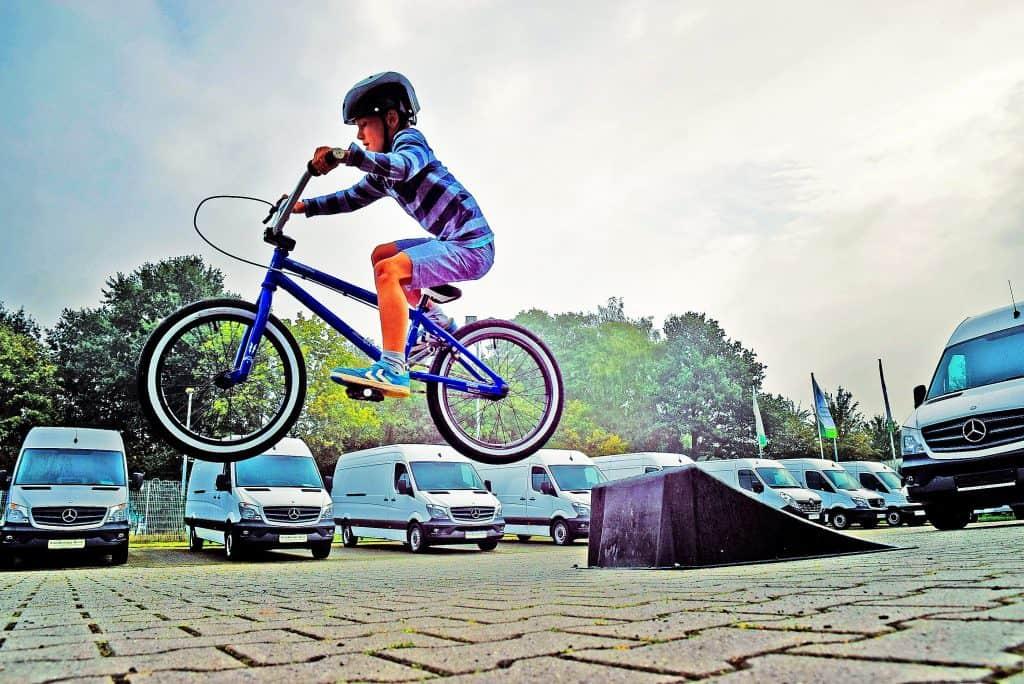 Imagem mostra um menino saltando de uma rampa com uma bicicleta, com uma fileira de vans ao fundo.