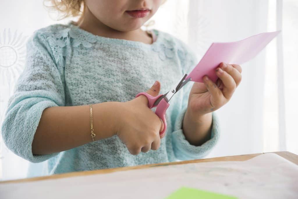 Imagem mostra mãos de menina usando tesoura escolar para cortar pedaço de papel rosa.