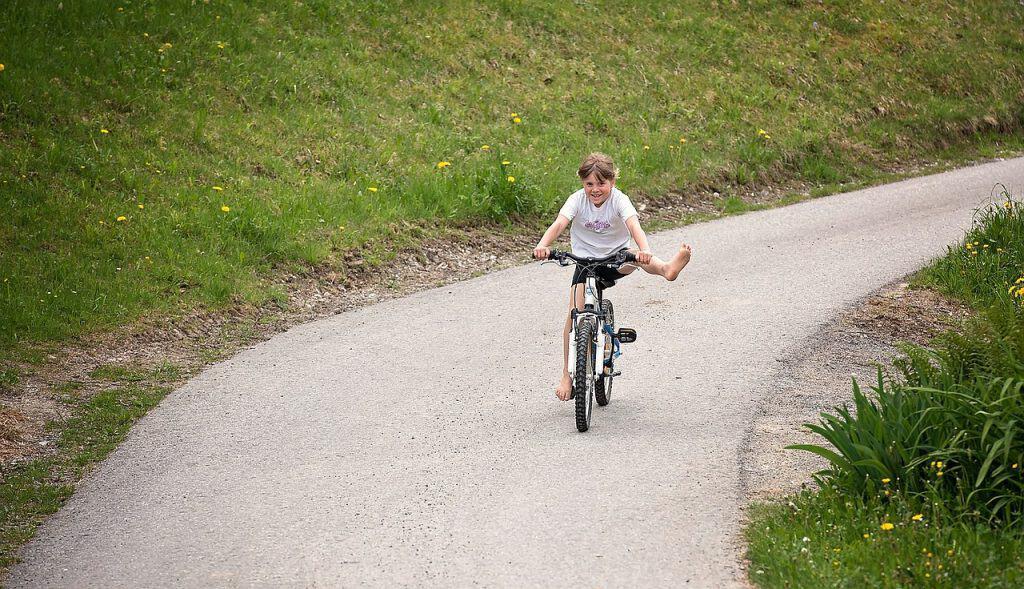 Imagem de criança andando de bicicleta com pé esticado.