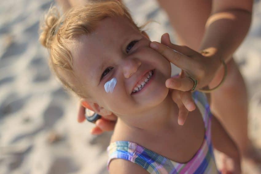Imagem de criança sorrindo passando protetor solar no rosto.